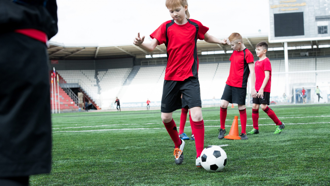 Full length portrait of junior football team practicing in stadium focus on boy leading ball in foreground, copy space